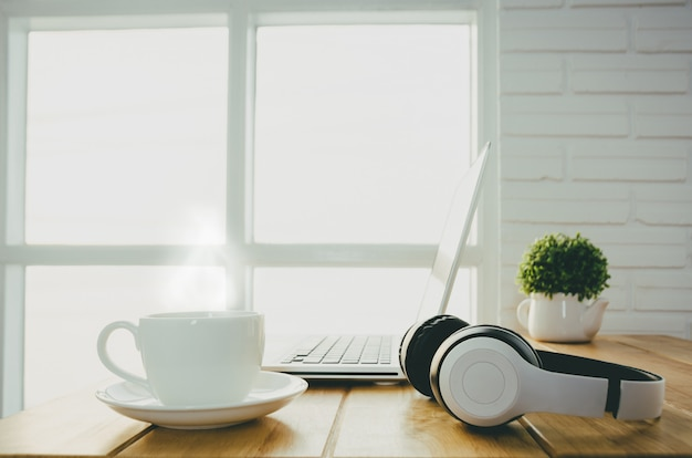Faccia colazione con una tazza di caffè caldo sul tavolo in ufficio che ha un computer portatile.