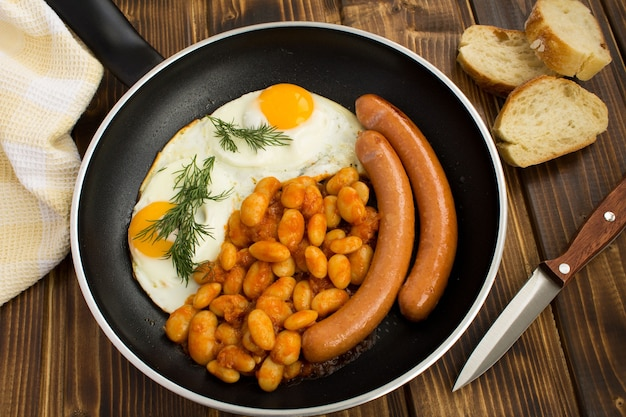 Prima colazione con uova, fagioli e salsicce sulla padella nera
