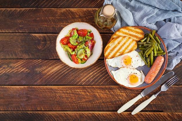 Prima colazione con uova, salsiccia alla griglia, fagiolini e pane tostato su legno