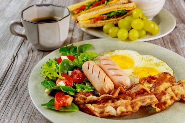 Colazione con uova, salsicce, pancetta e tazza di caffè.