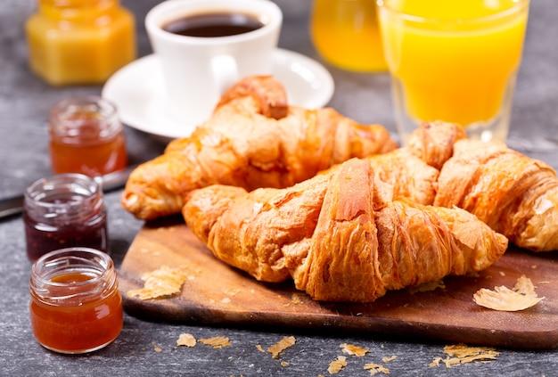 Colazione con croissant freschi e caffè sul tavolo scuro
