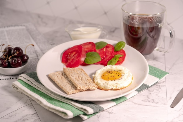 Colazione con uovo fritto, pomodori e pane croccante su un piatto con un drink su un tavolo