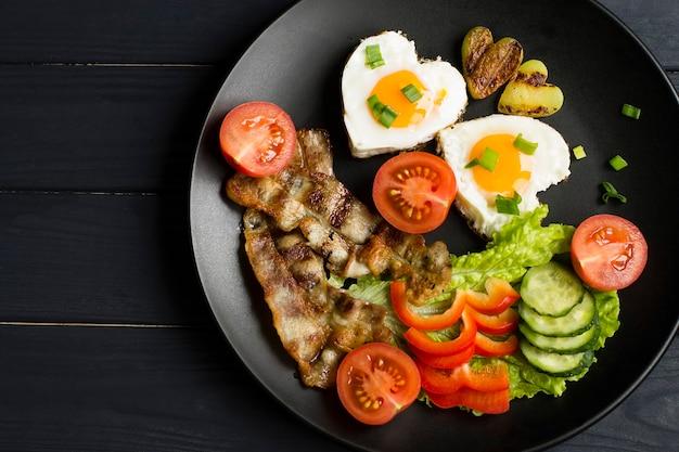 Colazione con uova fritte, pancetta e verdure fresche. in un piatto nero, su uno sfondo di legno.