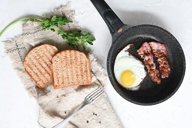 Prima colazione con uova fritte, toast e caffè su sfondo bianco.