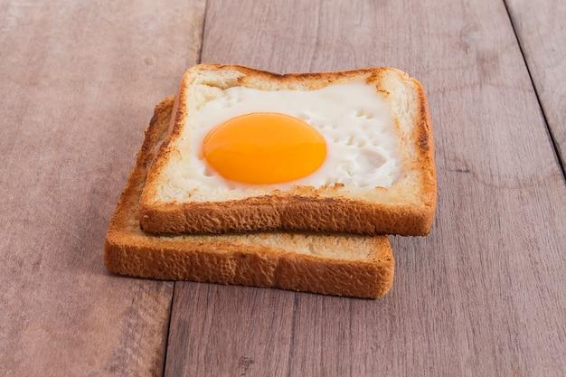 Colazione con uova fritte, toast sul tavolo di legno.