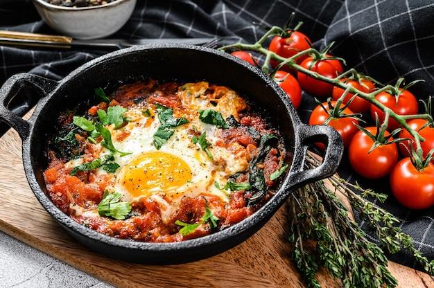 Prima colazione con uova fritte, pomodori. shakshuka in padella. piatti tradizionali turchi. sfondo grigio. vista dall'alto.