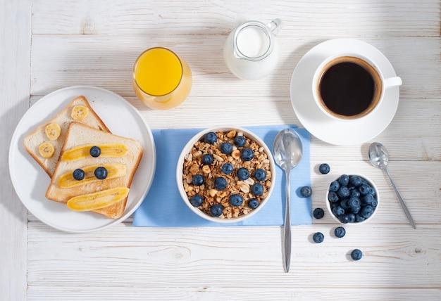 Colazione con muesli e mirtilli, caffè con succo d'arancia e toast al forno sul tavolo bianco
