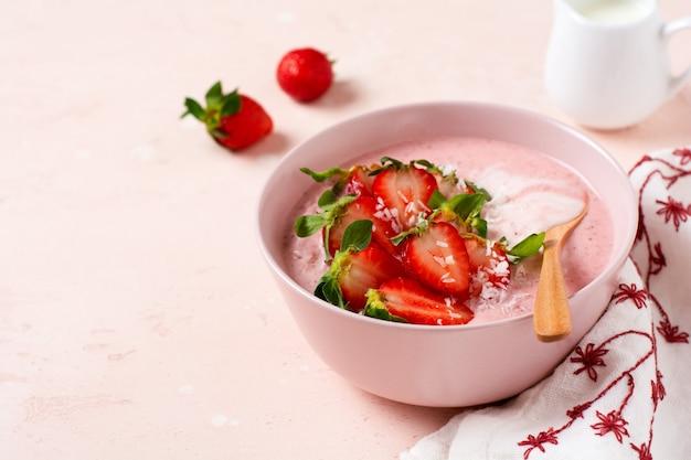 Colazione con frullato di muesli, cocco e fragole in una ciotola su uno sfondo rosa chiaro. menu dieta primaverile. vista dall'alto.