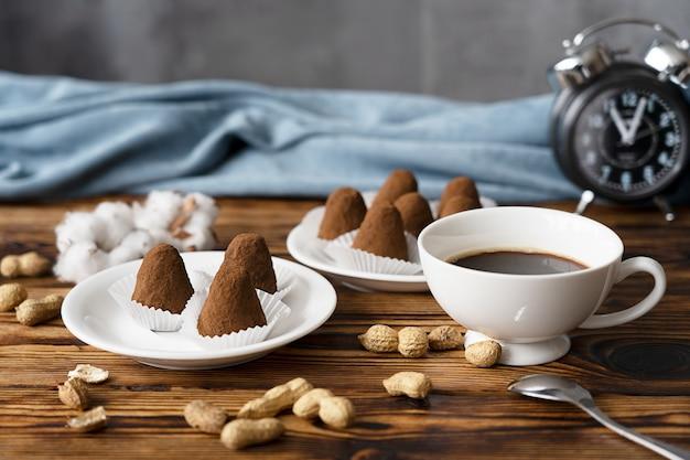 La colazione con tartufi di cioccolato fatti in casa con arachidi e una tazza di caffè servita sulla tavola di legno