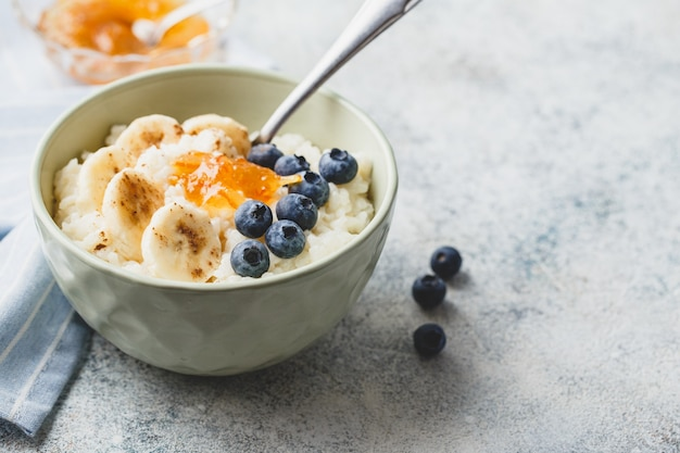 Colazione con porridge di riso al latte con banans, marmellata di mirtilli e arance, budino di riso cremoso o riz au lait francese in una ciotola.