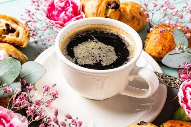 Colazione con mini panino di croissant freschi con cioccolato e tazza di caffè sulla superficie blu turchese