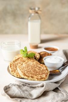 Colazione con frittelle di farina d'avena con yogurt alla marmellata e latte non caseario concetto di cibo vegetariano sano