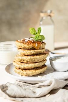 Colazione con frittelle di farina d'avena con yogurt alla marmellata e latte vegetale