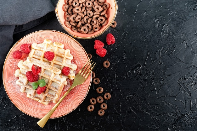 Colazione con cialde e una ciotola di cereali al cioccolato su sfondo nero. appartamento laico, vista dall'alto, copia dello spazio.