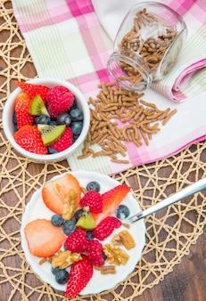 Colazione con yogurt, lamponi fragole e cereali