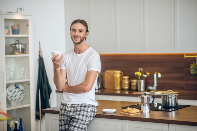 Prima colazione. giovane uomo in homewear in piedi in cucina con una tazza di caffè in mano