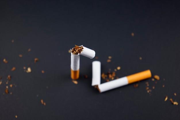 Rompere distruggere le sigarette fumando tabacco piatto giaceva su sfondo nero grunge texture