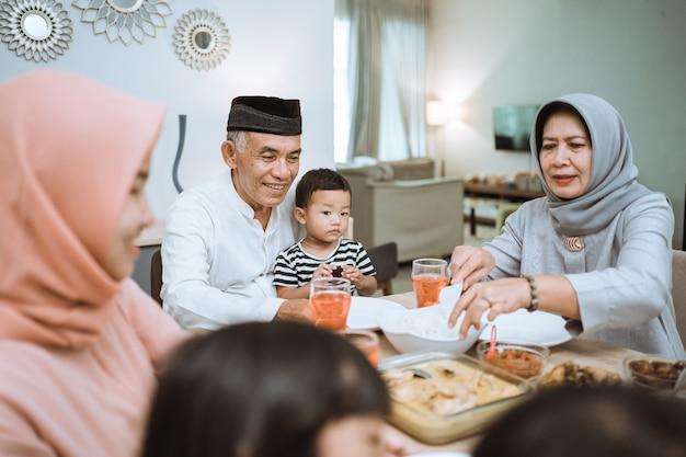 Rompere il digiuno. asiatico musulmano con hijab cenando iftar insieme a casa seduti sul tavolo da pranzo