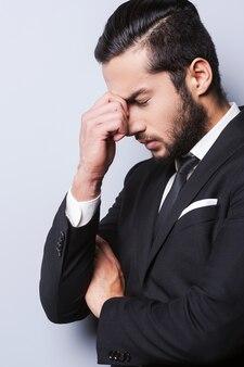 Rottura dallo stress. giovane frustrato in abiti da cerimonia che tocca la testa con le dita e tiene gli occhi chiusi mentre sta in piedi su uno sfondo grigio