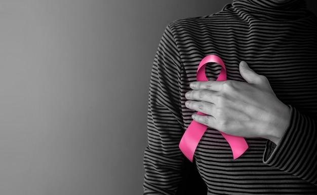 Concetto di campagna di consapevolezza del cancro al seno. assistenza sanitaria femminile. nastro rosa commovente della donna
