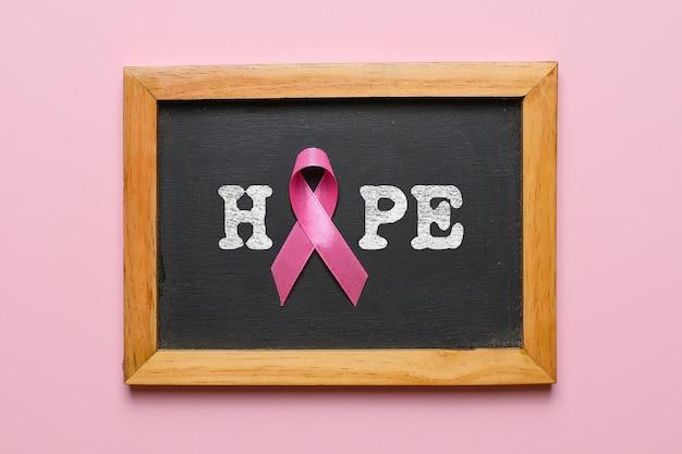 Concetto di layout flatlay di consapevolezza del cancro al seno su sfondo rosa