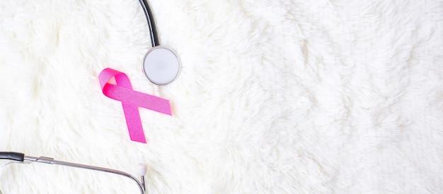 Consapevolezza del cancro al seno, nastro rosa con stetoscopio su sfondo bianco per sostenere le persone che vivono e le malattie. concetto di salute della donna e giornata mondiale del cancro