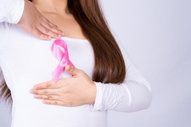 Nastro di consapevolezza del cancro al seno sul petto della donna e facendo autoesame su grigio