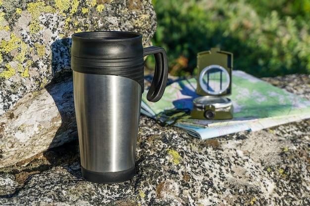 Un attimo di respiro: una mappa, una bussola e una tazza termica su una pietra su uno sfondo naturale