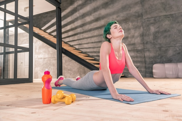 Respirando lentamente. donna magra dai capelli verdi che respira lentamente mentre si gode lo yoga al mattino