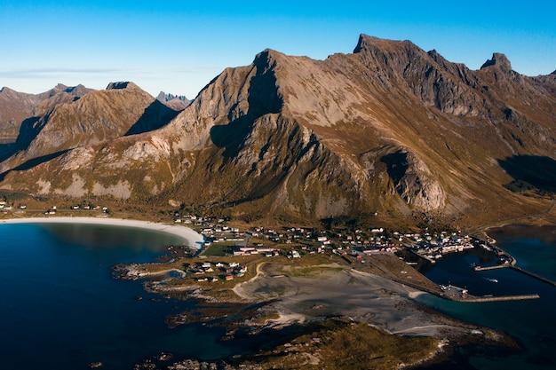 Ripresa aerea mozzafiato del paesaggio montuoso con alte montagne rocciose e l'oceano