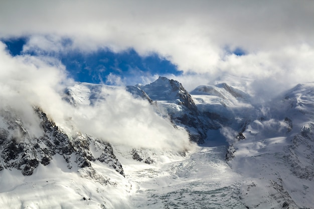 Vista aerea mozzafiato del picco di montagna del monte bianco coperto di neve splendente, ghiaccio e ghiacciai sotto il cielo blu con nuvole bianche gonfie sul lato francese delle alpi in una fredda giornata di sole invernale