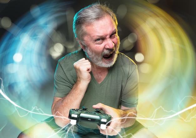 Nuova vita mozzafiato. uomo anziano in possesso di un controller per videogiochi isolato su sfondo colorato. pieno di emozioni. attività di svago. ha la peggior squadra del videogioco. cercando di ottenere il livello più alto.