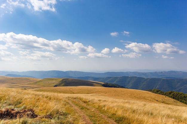 Vista mozzafiato di una valle di montagna sotto un cielo nuvoloso blu all'alba