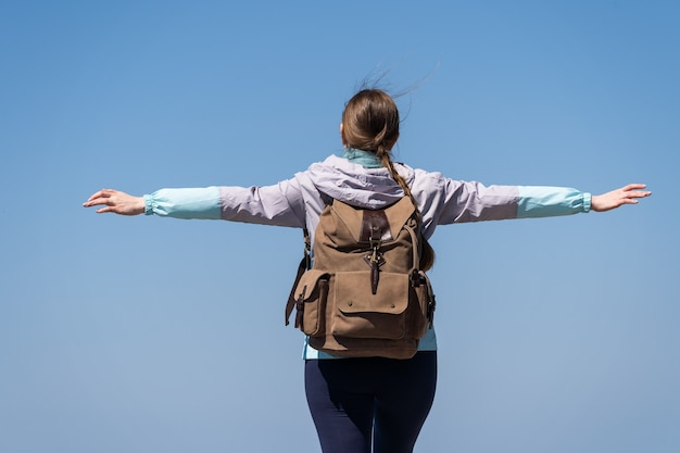 Panorami mozzafiato da una grande altezza una donna con le braccia aperte si erge su un'alta montagna ...