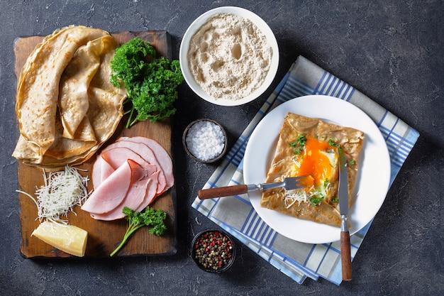 Crêpe bretone, galette di grano saraceno bretonnes con uova al sole, formaggio, prosciutto su un piatto bianco su un tavolo di cemento con ingredienti su un tagliere, vista dall'alto, flatlay