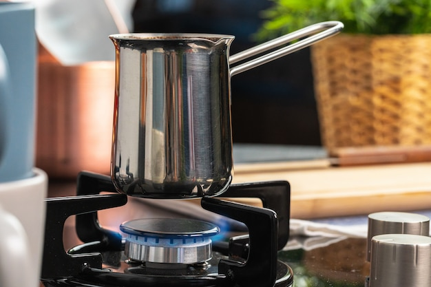 Prepara il caffè in un tacchino d'acciaio sulla cucina a gas