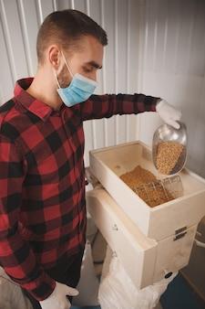 Il birraio che versa i semi dell'orzo nel mulino per il grano nel suo birrificio