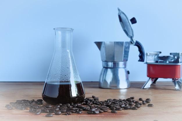 Erogazione di caffè caldo in tubo da laboratorio con chicco di caffè sul tavolo di legno.