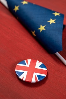Brexit, bandiera dell'unione europea con la bandiera della gran bretagna su un'icona di giacca insieme su una superficie di legno rossa.