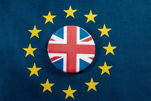 Brexit, bandiera dell'unione europea con la bandiera della gran bretagna su un'icona di giacca insieme su un tavolo.