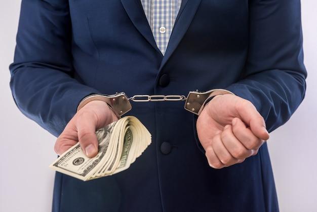 Corruzione o concetto di corruzione le mani maschili tengono le banconote in dollari in manette. penale