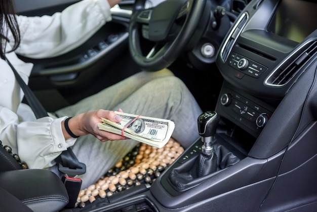 Corruzione. donna seduta al posto di guida e dando un pacco di dollari