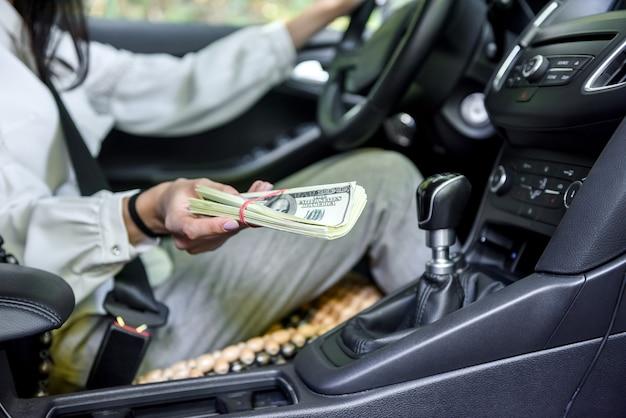 Corruzione. donna che si siede nel sedile del conducente e che dà il pacco del dollaro