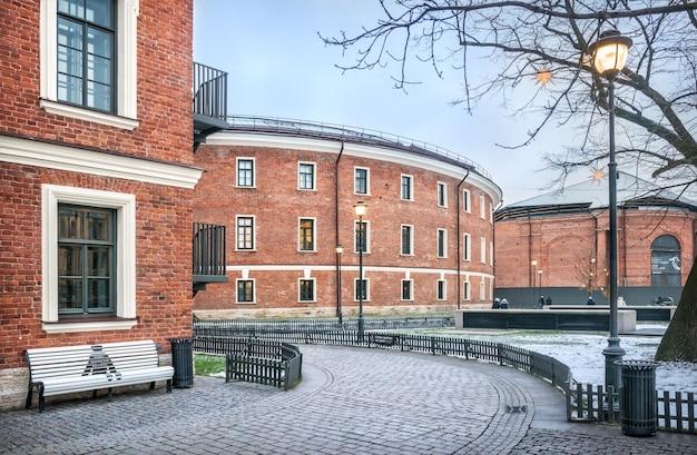 Edificio in mattoni di new holland a san pietroburgo e una panchina bianca