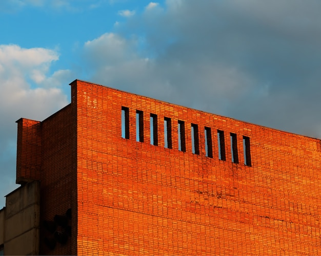 Edificio in mattoni con lo sfondo dell'architettura di lacune drammatiche