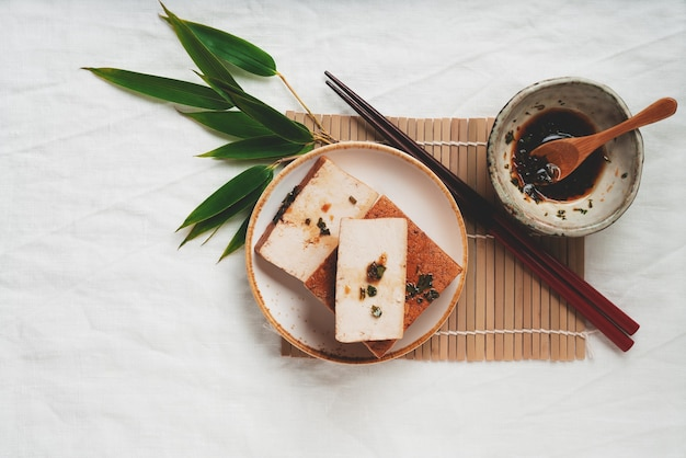 Mattone di formaggio di tofu somoked biologico con salsa di soia e foglie di bambù. lay piatto. vista dall'alto. concetto di spuntino vegano