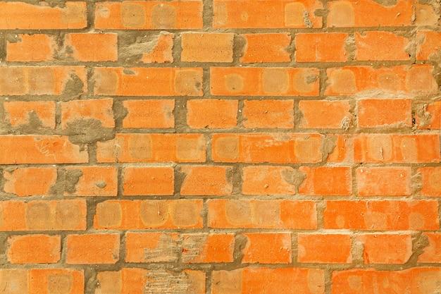 Trama di muro rosso mattone. sfondo di una nuova casa con mattoni a vista con cemento.