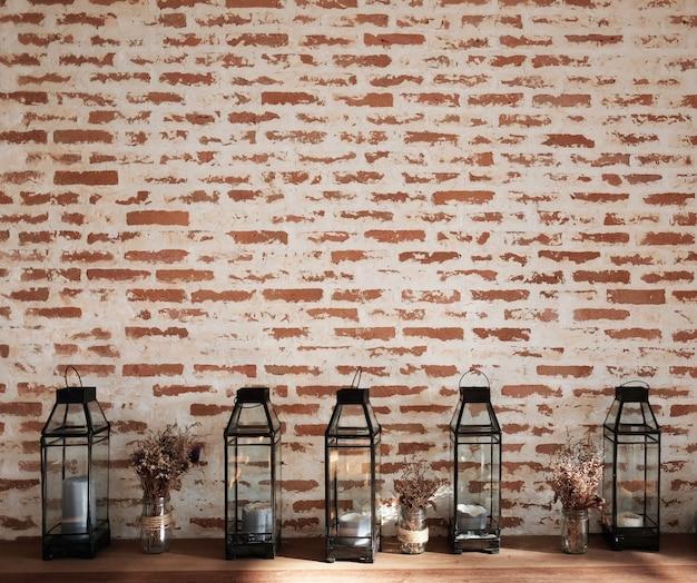 Grunge texture muro di mattoni con lanterna vintage e fiori secchi sulla console di legno.