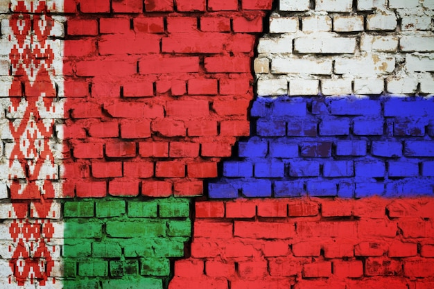Muro di mattoni con una bandiera della bielorussia e della russia