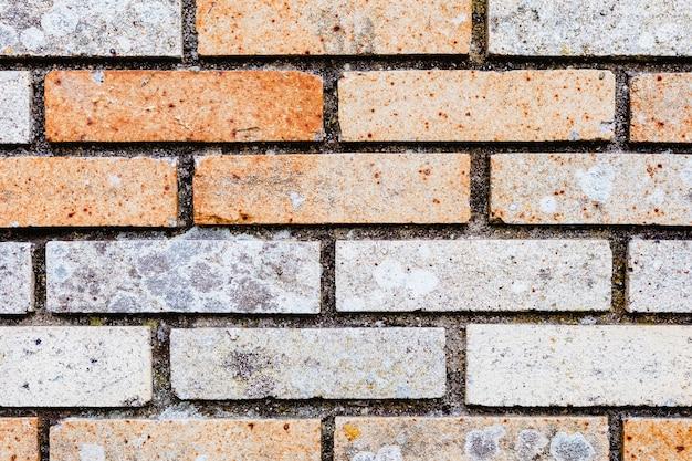 Muro di mattoni con mattoni arancioni e grigi da utilizzare come sfondo.
